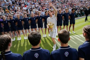 Andy Murray walks off court with the winners trophy