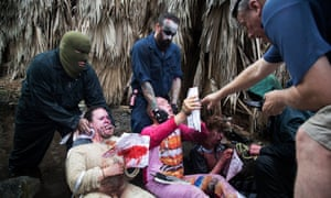 Guests read a waiver for McKamey Manor as they sit in storm drain run-off.