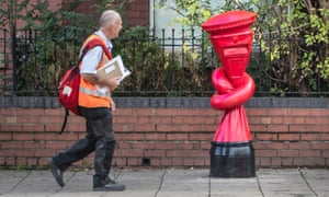 A postal worker walks past a postbox tied in a knot, an artwork by Alex Chinneck in Sheffield