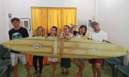 Filipino teacher Giovanne Branzuela (L) posing with his surfboard, once owned by big wave surfer Doug Falter who lost it while surfing in Hawaii, along with his villagemates on Sarangani island in the Philippines