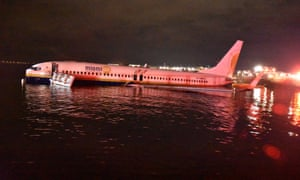 Passengers escape after plane skids off runway into river in