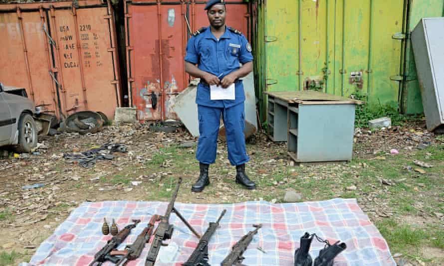A Burundian policeman displays weapons seized during an operation in the Musaga neighborhood of Bujumbura
