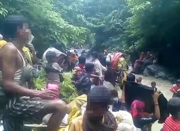 People apparently fleeing with their possessions in Myanmar