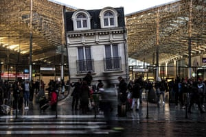 Commuters at Gare du Nord station by the artwork Maison Fond by Argentinian artist Leandro Erlich
