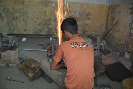 Sparks fly as a child works on surgical tools at a workshop in Sialkot, Pakistan