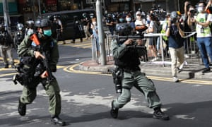 Riot police shoot pepper-spray balls to disperse protesters during a rally against a new national.