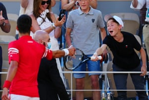 Novak Djokovic hands his racquet to an excited young fan after his victory.