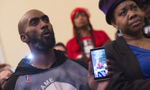 Flint resident Demeceo Braylock shows a photo of his nephew during a news conference on Capitol Hill in Washington.