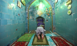 A man prays inside the shrine of Imam Mahdi at the Wadi al-Salam cemetery.