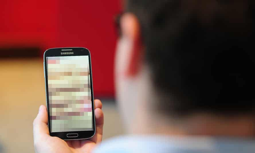 A man looks at (pixelated) pornography on a smart phone.