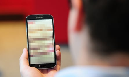 A man looking at a mobile phone with its screen blurred out