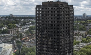 Debris hangs from the blackened exterior of Grenfell Tower.