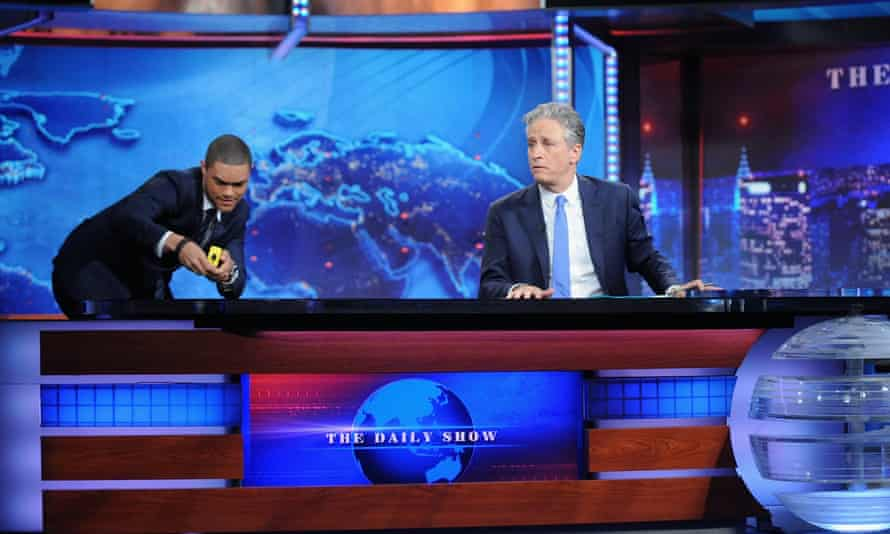 Trevor Noah measures out his new desk while Jon Stewart looks on.
