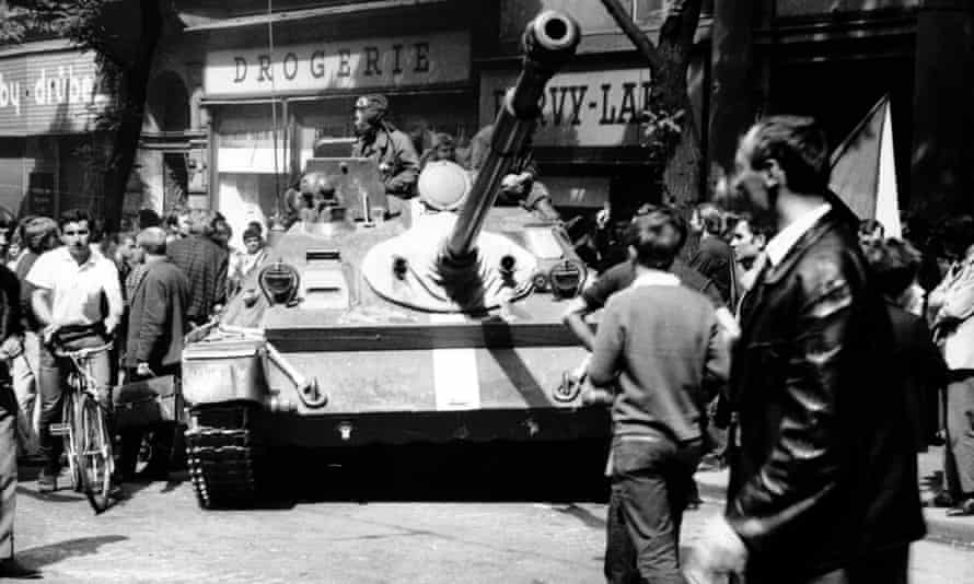 A man on a bicycle passes a tank in Prague in 1968