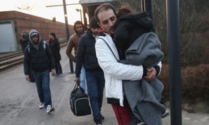 Refugees, many of them from Syria, walk to police vans in Padborg, Denmark. MPs are expected to pass tough new laws designed to make the country 'less attractive' to refugees.