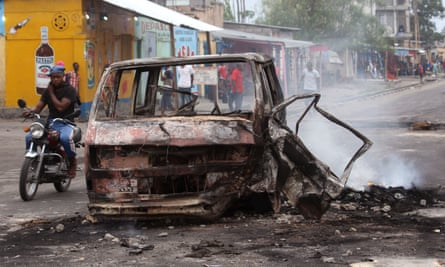 A man rides past a burned-out car in Kinshasa