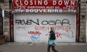 A woman in a face mask walks past a shuttered shop on Oxford Street