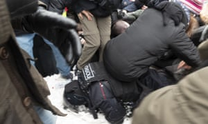 Demonstrators sit on a policeman lying in the snow in Moscow