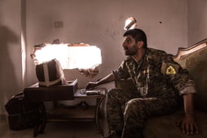 A YPG soldier from the SDF extinguishes his cigarette in front of a hole in the wall through which he is watching the neighborhood