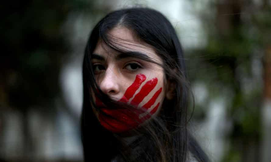 A Lebanese woman with her face painted with a red hand
