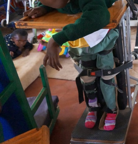 A child held in a standing position as part of physical therapy at Compassionate Hands