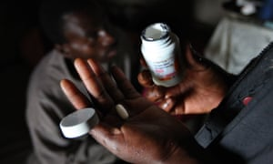 A woman hands an anti-retroviral tablet to her husband in Mkhulamini, photographed in 2009.