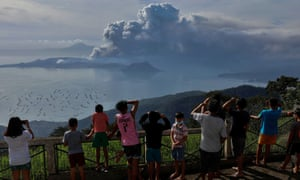 Residents of Tagaytay city look out over the erupting volcano