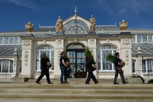 Horticulturalists carry saplings past the entrance to the Temperate House at Kew Gardens.
