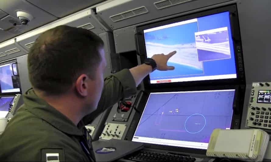 A US navy crewman aboard surveillance aircraft points out alleged Chinese construction on the reclaimed land of Fiery Cross Reef in the disputed Spratly Islands in the South China Sea on 21 May.