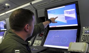 A US navy crewman aboard a surveillance aircraft viewing a computer screen purportedly showing Chinese construction in the disputed Spratly Islands.