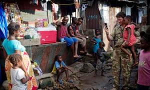 Brigadier Charlie Herbert from the UK's Ebola taskforce talks to a young Ebola survivor in Magazine Wharf, a Freetown slum