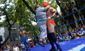 An employee of Mexico's health ministry embraces a wrestler during an exhibition bout to mark the start of a campaign to fight obesity in Mexico City.