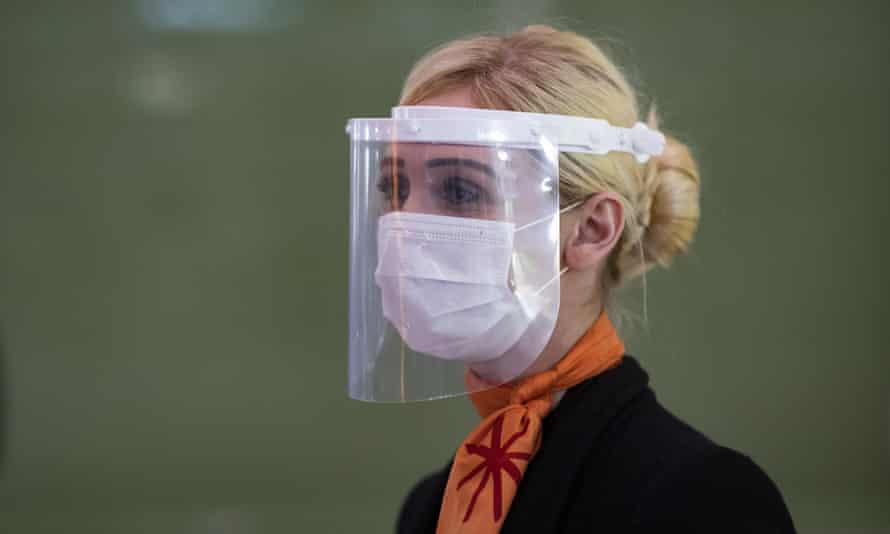 A member of staff at Charles de Gaulle airport, Paris, wearing a face mask and visor