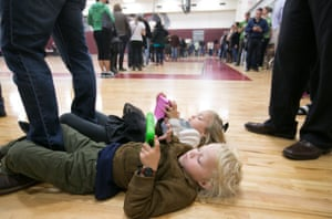 Atlanta, GeorgiaMerrick, 4, (front) and Savannah Little, 5, entertain themselves with electronic devices while waiting in line with their parents on election day