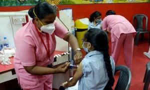 Students of a private school receive a Covid vaccine in Kolkata, India.