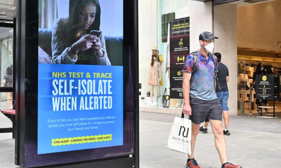 A shopper walks past an advertisment for the UK government's NHS Test and Trace system