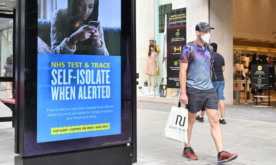 A shopper walks past an advertisement for the NHS test and trace system.