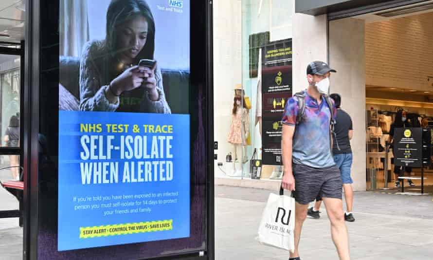 A shopper walks past an advertisment for the NHS test and trace system in Regent Street, London