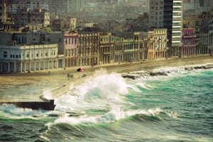 An old American car rolls down the Malecón in Havana as the waves kick up.
