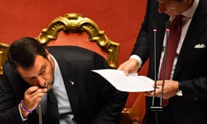 Salvini kisses a rosary as Conte delivers his speech to the Italian Senate.