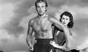 A bare-chested Tarzan holds a knife while Jane, standing behind him, hold onto him