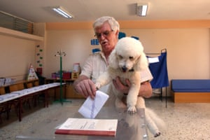 Athens, Greece A man, holding his dog, casts his vote at a polling station during the country's general election