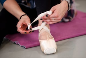 tying the ribbon on a pair of ballet shoes