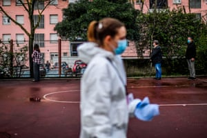 A cleaning employee wearing a protective suit walks past people queuing to vote in the Portuguese presidential election at the Telheiras school.