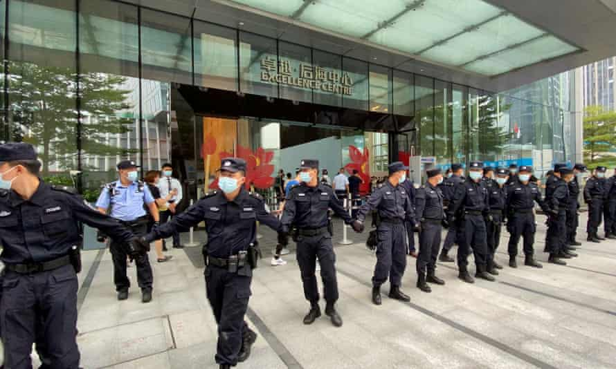 Security personnel form a human chain as they guard outside the Evergrande's headquarters, where people gathered to demand repayment of loans and financial products, in Shenzhen on Monday.