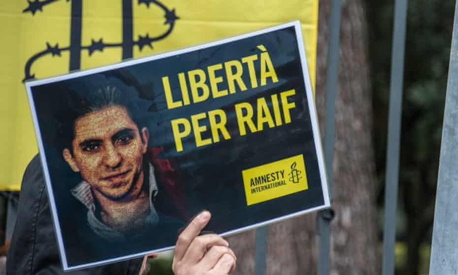 Sign depicting Raif Badawi held by Amnesty International activists