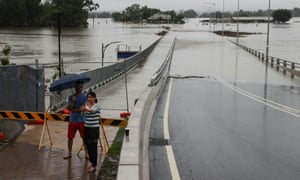 A woman takes a selfie in front of a flooded bridge in the suburb of Windsor as the state of New South Wales experiences widespread flooding and severe weather, in Sydney, Australia, March 22, 2021.