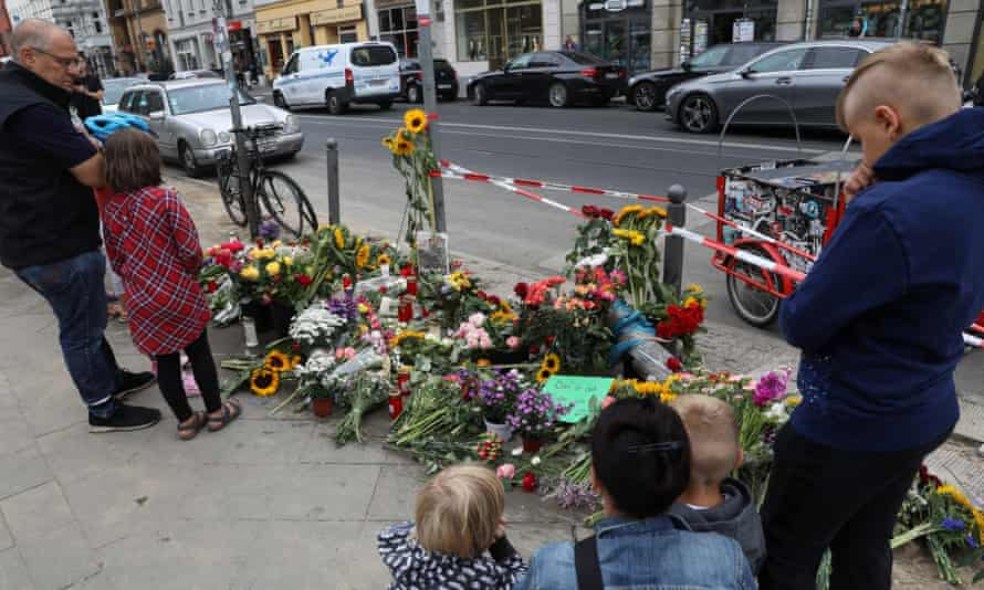 People mourn at the site of an accident in Berlin, in which four people were killed and three seriously injured when a SUV car crashed into a group of pedestrians.
