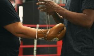 man lacing boxing glove