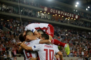 Mathieu Valbuena of Olympiacos celebrates with team mates after he scores his sides second goal from the penalty spot.
